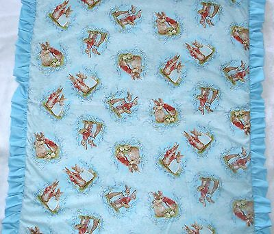 Beatrix Potter Mr and Mrs Bunny tossed on a turqoise cot quilt