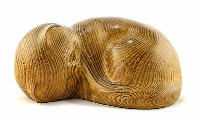 A hand carved curled up cat sculpture. Signed P.Elmore Solid wood