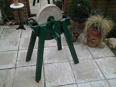 antique sharpening stone wheel on wooden stand, grinding wheel wet stone