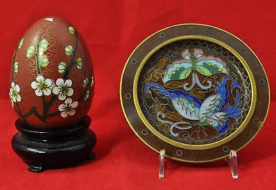 A cloisonne egg on a stand and a  small plaque featuring butterflys