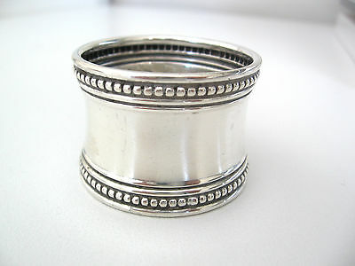 Cotton-reel shaped sterling silver napkin ring with beaded edges.  No monogram