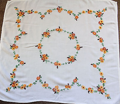 Vintage white hand embroidery tablecloth with orange and yellow flowers.