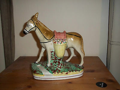 Antique Staffordshire pottery donkey/mule with wicker panniers containing fruit.