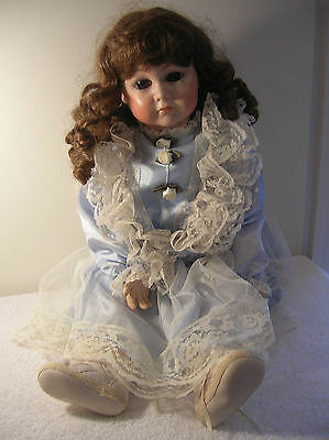 Collectible doll with bisque face, moveable legs/arms with beautiful dress