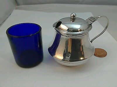 A sterling silver mustard pot with blue glass liner London 1911.
