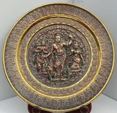 An Indian brass and copper repousse plaque decorated with three deities, 23.5cm