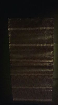 A dark brown Guinea  brocade material with patterns..