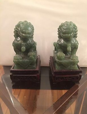 two old green jade chinese lions figures on carved wooden bases. Excellent