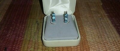 10k white gold earrings with 3 cttw in blue topazs.