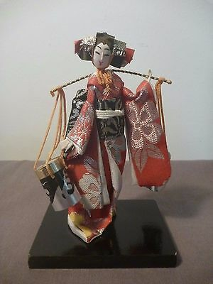 Japanese Cloth/paper doll on wooden base, bucket carrier
