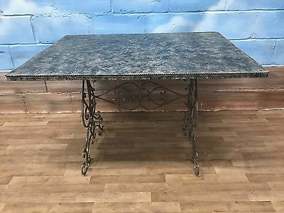 Very unusual metal garden dining table with decorative wrought iron base.