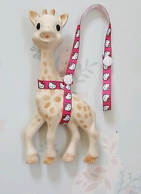 Sophie The Giraffe Harness Pink Ribbon with Hello Kitty Design & White Poppers.