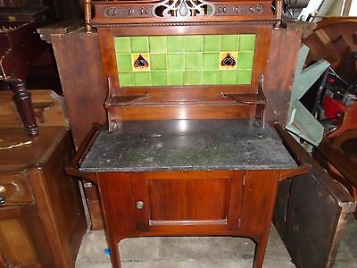 small walnut buff with black marble top green tile on back piece