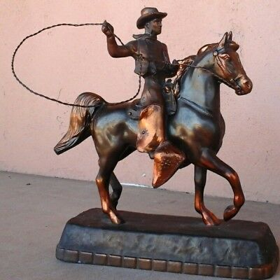 Cast copper cowboy with lasso on horse. 11 in high. Base 9 x 3 in.