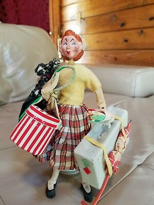 Vintage doll holding her dog, flowers, suitcase, hat box and umbrella