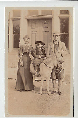 Parents Beside Smart Little Girl on Donkey, In Front of Large House - RPPC (P48)