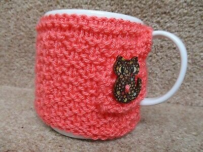 HAND KNITTED  MUG COSY  in CORAL WITH A PRETTY CAT BUTTON FASTENING