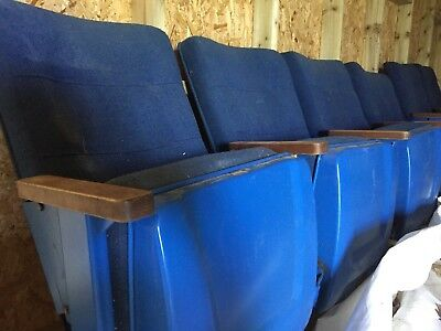 Old folding cinema seats with aisle letters and seat numbers