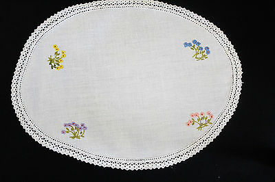 Vintage off-white linen oval cloth/doily with hand embroidered flowers.