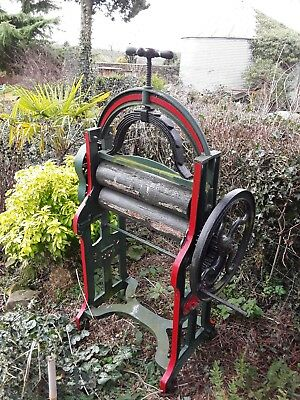 Vintage washing mangle with cast iron base sides and top. Wooden rollers.