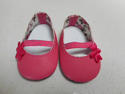 a Pair of Battat Pink Doll Shoes - pink flower to side of shoe