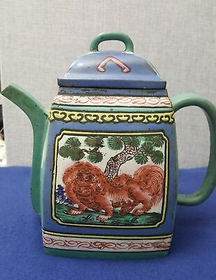 An enamelled Y hsing teapot. The side panels have foo dogs an pine,on