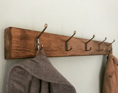 Beautiful rustic coat rack with a wooden back board and vintage style hooks