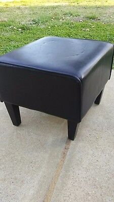 dark leather foot stool with hidden zip up compartment underneath.