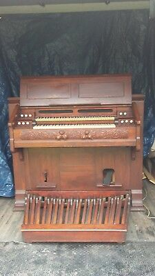 Reed organ with 2 manuals and full bass pedals. Made by Estey