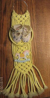 yellow nursery macrame picture with booties and rocking horse