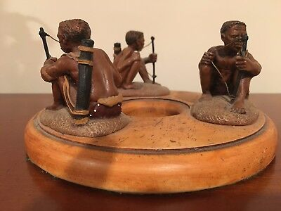 Beautiful carving three African tribal men hunting in a circle
