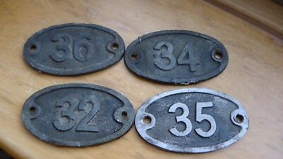 Four oval lead number number plates from railway carriage lighting battery cases