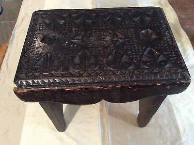 A small rustic antique carved wooden stool