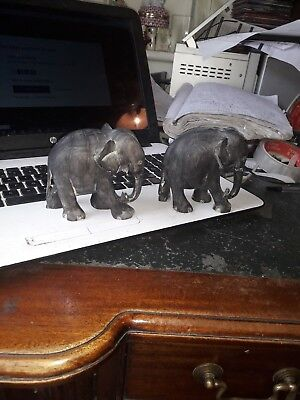2 charming small models of elephants black either wood or some sort of resin