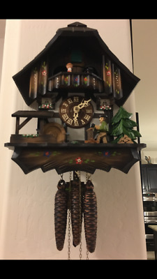 Vintage musical cuckoo clock with multiple moving figures.