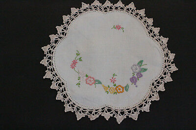Vintage white round linen doily with pink, purple and yellow flowers.