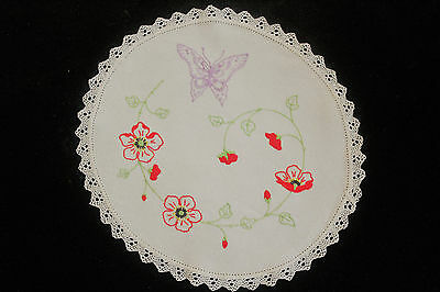 Vintage beige round cloth with embroidered butterfly and red flowers.