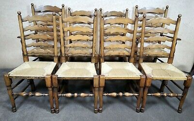 A Set Of Eight Oak And Rush Seated Ladder Back Dining Chairs