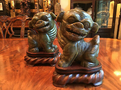 A Pair Antique Chinese Carved Green Jade Foo Dogs with Craved Rosewood Stands.