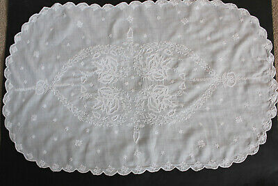 Vintage oval white tray cloth with scalloped edges and white embroidery.