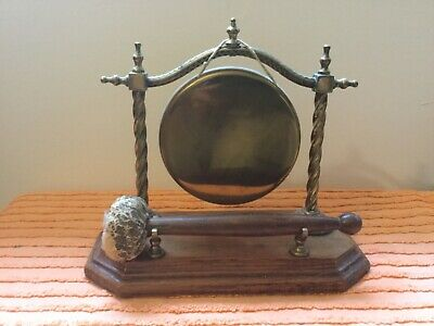 Antique brass dinner gong on wooden base with striker