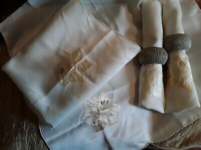 Four cream napkins and two silver napkin rings/holders