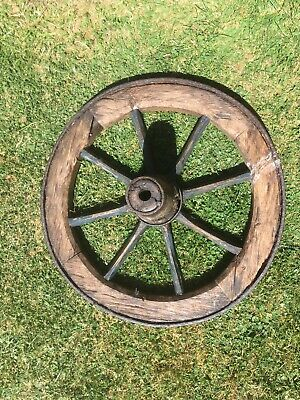 very old wooden cart/wagon wheel with metal rim