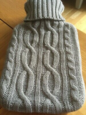 Small hot water bottle with grey woolly cover. Never used.