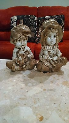 VINTAGE PAIR OF CERAMIC BOY AND GIRL FIGURINES OR STATUES HOLDING BABY AND DOG