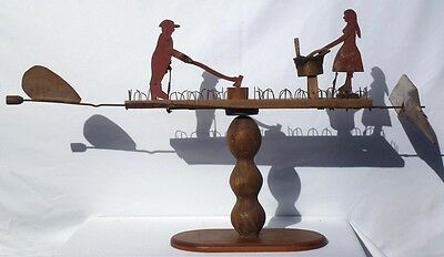 A primitive whirligig with a man chopping wood and a woman scrubbing laundry.