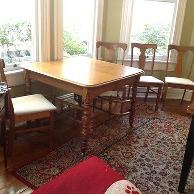 Antique oak Eastlake dining table with four chairs