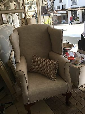 wingback chair newly upholstered in Natural linen and decorative piping