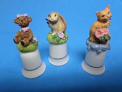 Rabbit, A Cat, And A Teddy Bear .all Sitting On Top Of Porcelain Thimbles