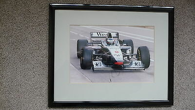 A HAND SIGNED AND FRAMED COLOUR PHOTO OF MIKA HAKKINEN RACING A McLAREN
